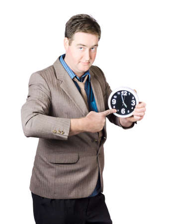 Over white portrait of a business person pointing to the 5pm time on an office clock. Overtime
