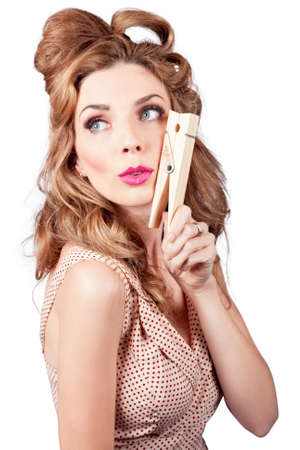 quirky: Quirky photo of a pretty pinup housewife wearing pink lipstick with big fifties hairdo, holding large cleaning peg on white background