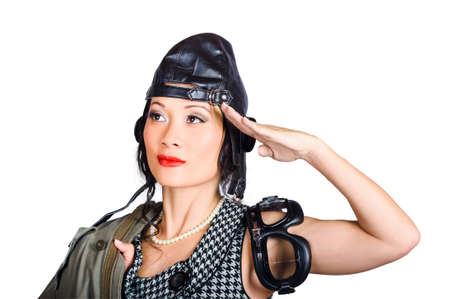 fighter pilot: Isolated photograph of a female military officer wearing fighter pilot hat saluting to answer a command in all pin-up class. Flight training school Stock Photo