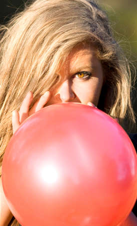 inflating: Blond Haired Young Woman Inflating Red Party Balloon. Stock Photo