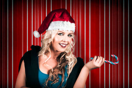 lollys: Retro Christmas Girl Holding Candy Cane While Pointing To Sweet Copyspace On Striped Background