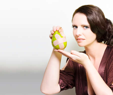 bruised: Beautiful woman wrinkling her nose in disgust at an unappetising pear with a bandaid cross in a Bruised fruit or unappealing healthy eating concept