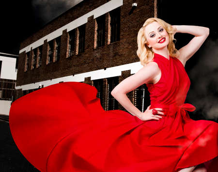 back alley: Portrait of a beautiful sexy blond girl wearing a long elegant red dress when dancing in a urban back alley with stylish hair and make up Stock Photo