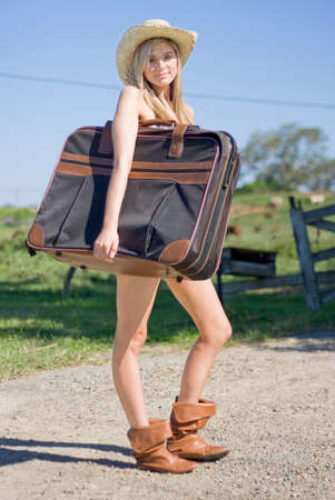 vacate: Full Body Portrait Of A Sexy Blond Female Tourist Holding Her Luggage In A Green Countryside Vacation