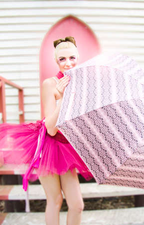 bashfulness: Beautiful Young Ballerina Woman In Pink Lace Tutu Holding A Umbrella Poses In Front Of The Steps Of A Church Door In A Rain Dance Representation