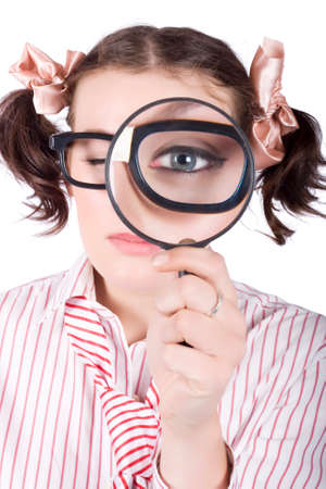 crime solving: Young caucasian businesswoman wearing eyeglasses looking with one eye through magnifying glass Stock Photo