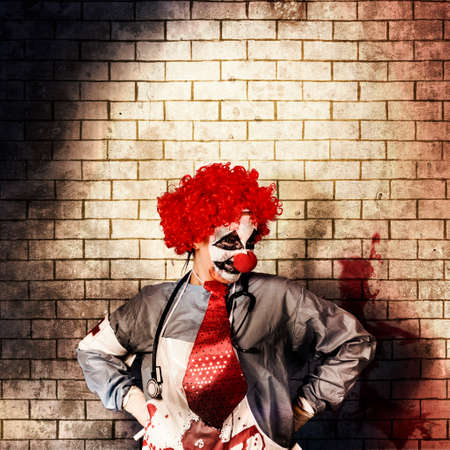 psychopath: Sinister gothic hospital clown standing on grunge brick wall with masthead copy space. Psychopath surgeon