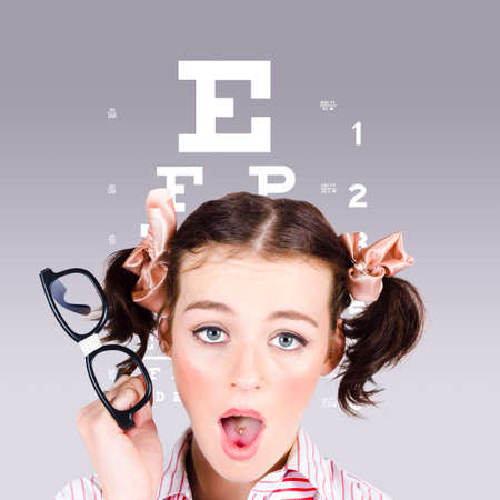 shortsighted: Funny portrait of a blind nerd woman holding glasses while struggling to read an optometry eyesight test chart Stock Photo