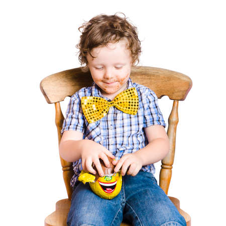 chocolaty: Cute young boy with chocolaty mouth opening Easter egg, white background