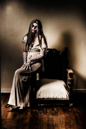 spooky house: Evil horror photograph of a ghostly vampire woman sitting on old armchair in haunted house interior. Grunge nightmare Stock Photo