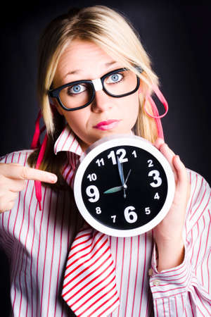 tardy: Concerned Business Woman In Dork Glasses Pointing To Delayed Black Office Clock In A Depiction Of Tardy Time Management