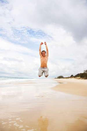 bounding: A Young Man Jumping For Joy On A Stormy Beach Shoreline, Taken: Bribie Island, Queensland, Australia