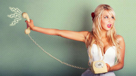 exasperated: Pop Art Portrait Of A Beautiful Blonde Pin-up Girl On Hold With Call Waiting Music Playing In A Depiction Of Poor Customer Service On Dotted Background Stock Photo