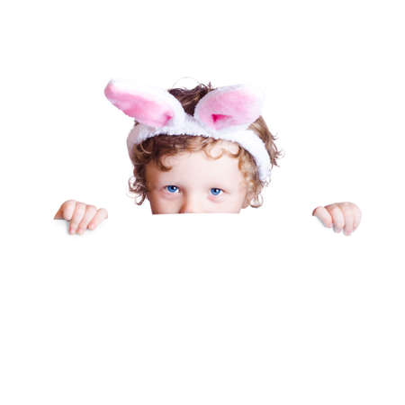 hands over ears: A boy with Easter bunny ears holding a white blank board