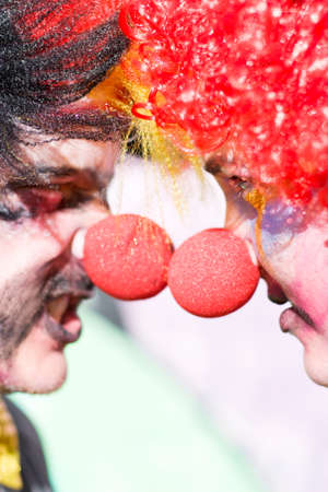 battling: A Couple Of Colorful Circus Clowns Stand Outside Opposite Each Other Head To Head In A Conflicting Confrontational Face Off Stock Photo