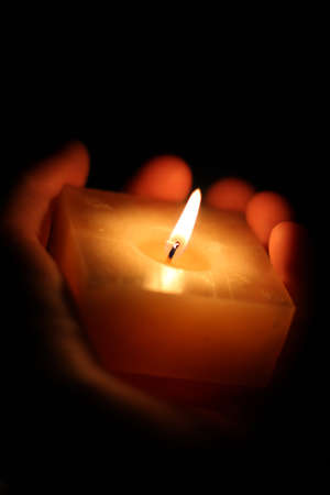 leading the way: A Square Candle Sits In The Palm Of A Lost Souls Hand Leading A The Way Though The Darkness Stock Photo