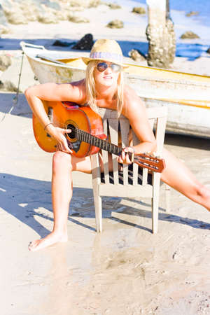 vacationing: Happy Smiling Vacationing Tourist Sitting On A Wooden Chair By The Ocean Shore Singing A Summer Song In A Playful Melody Of Happiness Stock Photo