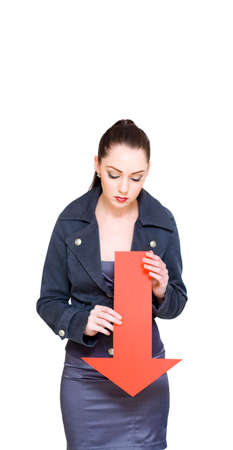 woman pointing: Business Woman Looking Down Holding Red Arrow In A Negative Symbol Of A Economic Downturn With A Plummeting Fall In The Share Or Stock Market Stock Photo