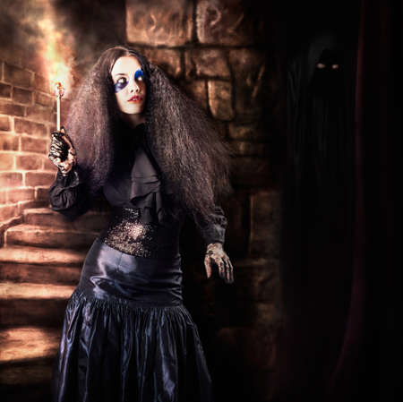medieval woman: Medieval photo illustration of a jester woman holding torch lantern while walking inside a dark stone staircase deep inside the basement of a vintage haunted castle. Halloween concept