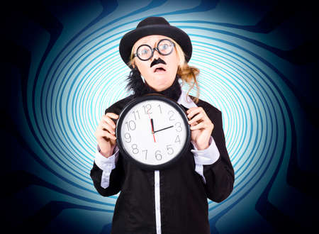 dismayed: Funny portrait of a nutty male science professor holding clock on blue time warp background