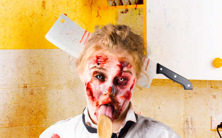 battered woman: Crazy sick monster cook licking wooden spoon inside yellow kitchen with meat cleaver through head. GMO food Stock Photo