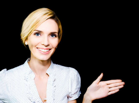 endorsement: Stylish beautiful blonde woman extending her hand and pointing in an endorsement of your product or advertisement as she gives it her personal sanction