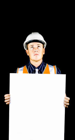 raises: Safety officer or construction worker wearing a hardhat holds a blank sign as he raises his eyes to additional copyspace on a black background above his head Stock Photo