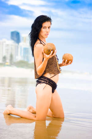 prettiness: Beautiful Shoreline Female Kneeling In Shallow Water Holding Two Coconuts With A Ethereal Expression Of Prettiness With A Beach City Background