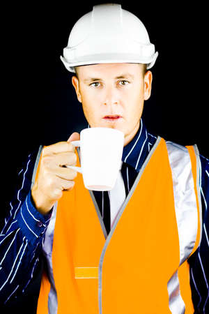 high visibility: Construction worker, architect or engineer dressed in a hardhat and high visibility jacket for his protection having a mug of coffee on his break Stock Photo
