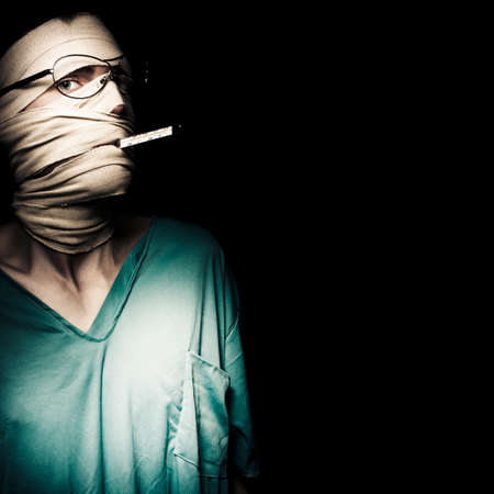 persons: Ill Man Wrapped In Bandages Holding A Thermometer In Mouth To Monitor Health Stability For Recovery Stock Photo