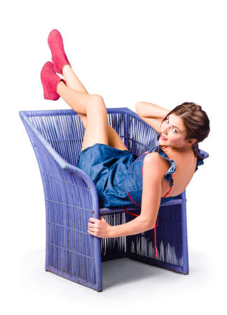 cane chair: Happy woman in blue denim dress kicking back on cane chair Stock Photo
