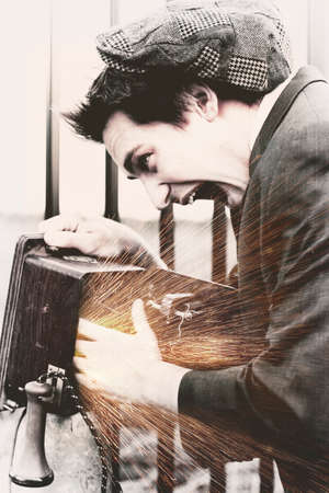 olden: Desiderated Photo Of A Vintage Man Putting His Hand In A Olden Day Wooden Box Telephone To Get A Electric Charge Zap In A Blast From The Past Concept