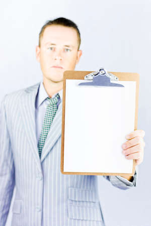 downgrade: Young businessman holding a clipboard with blank paper where you can place your own message Stock Photo