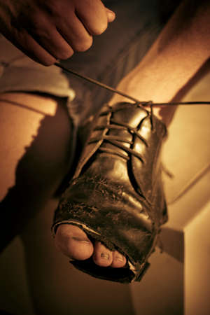 deprived: Underprivileged Boy Ties Up The Laces On His Shoes He Has Outgrown Stock Photo