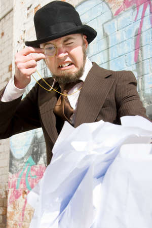 A Bearded Businessman Wearing A Bowler Hat Stares Through His Monocle In Anger At A Mound Of Scrunched Up Paperwork
