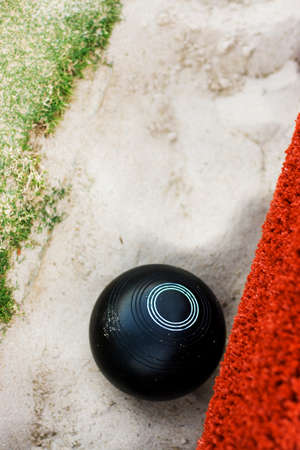 tragic: Vertical Image Of A Lawn Bowls Ball Lie In A Sand Gutter From A Rather Tragic Bowling Attempt