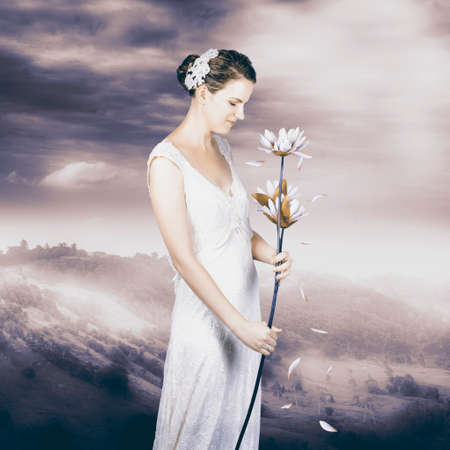 sentimental: Sentimental woman on mountain lookout wearing vintage wedding gown holding flower with falling petals Stock Photo