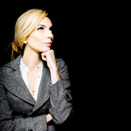 preoccupied: Preoccupied beautiful business woman in an elegant vintage outfit deliberating her choices as she stares up towards copyspace with her chin resting on her hand Stock Photo