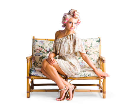 curlers: Beautiful young woman in dress and curlers sat on wooden couch or sofa, white background