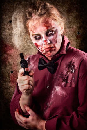 demented: Evil demented zombie with facial wounds and bloodshot eyes holding hand gun. Dead security Stock Photo