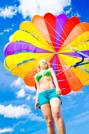parasailing: Low angle view of a young woman in a bikini standing beneath a colourful inflated parasail canopy with a harness against cloudy blue sky in summer
