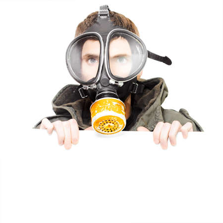 Sign of pollution and terror with a male army soldier wearing military gas mask holding blank empty copy space board in a place your notice of protest here