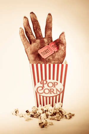 horror movies: Frightening Picture Of A Creepy Sawn Off Hand Poking Out Of A Striped Pop Corn Box Holding Two Cinema Movie Tickets In A Horror Movie Conceptual Stock Photo