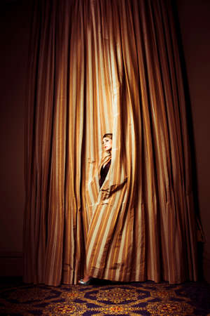 thespian: Theatre Performer peeking out through heavy gold curtains as she awaits her cue to make an entrance on stage
