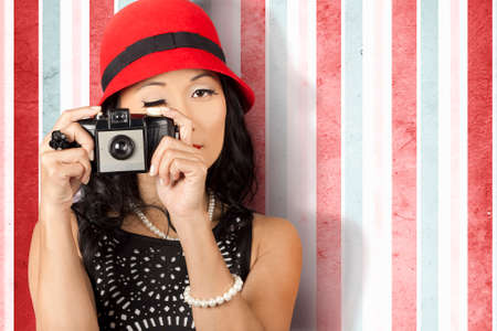 40s: Glamorous pin-up photographer girl wearing red hat and pearl jewellery holding retro film camera in 40s fashion. Focus on copyspace Stock Photo