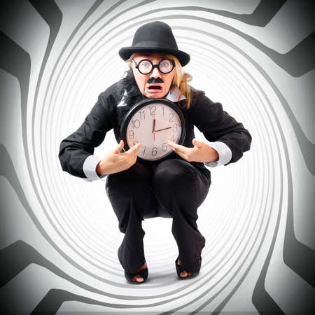 idiosyncratic: Vintage business man holding clock while stuck in a tight time pressured schedule. Time crunch concept
