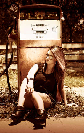 abandoned gas station: Woman Stops Off At A Old Abandoned Gas Service Station On Route 66 And Rests Against A Petrol Pump In Nostalgia Of 1950s Retro American Car Culture