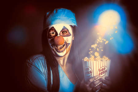 slasher: Scary zombie clown holding popcorn in cinema while watching a halloween horror movie. Slasher movies at the THEATER concept