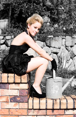 horticulture: Happy Woman Finding Serenity On A Garden Brick Wall Holding A Steel Watering Can Expressing Happiness In Horticulture (Black And White Background)