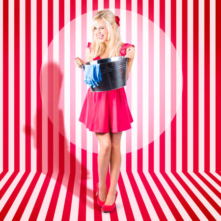housecleaning: Full body portrait of a cute retro house wife winking with washing up bucket. Domestic housecleaning services